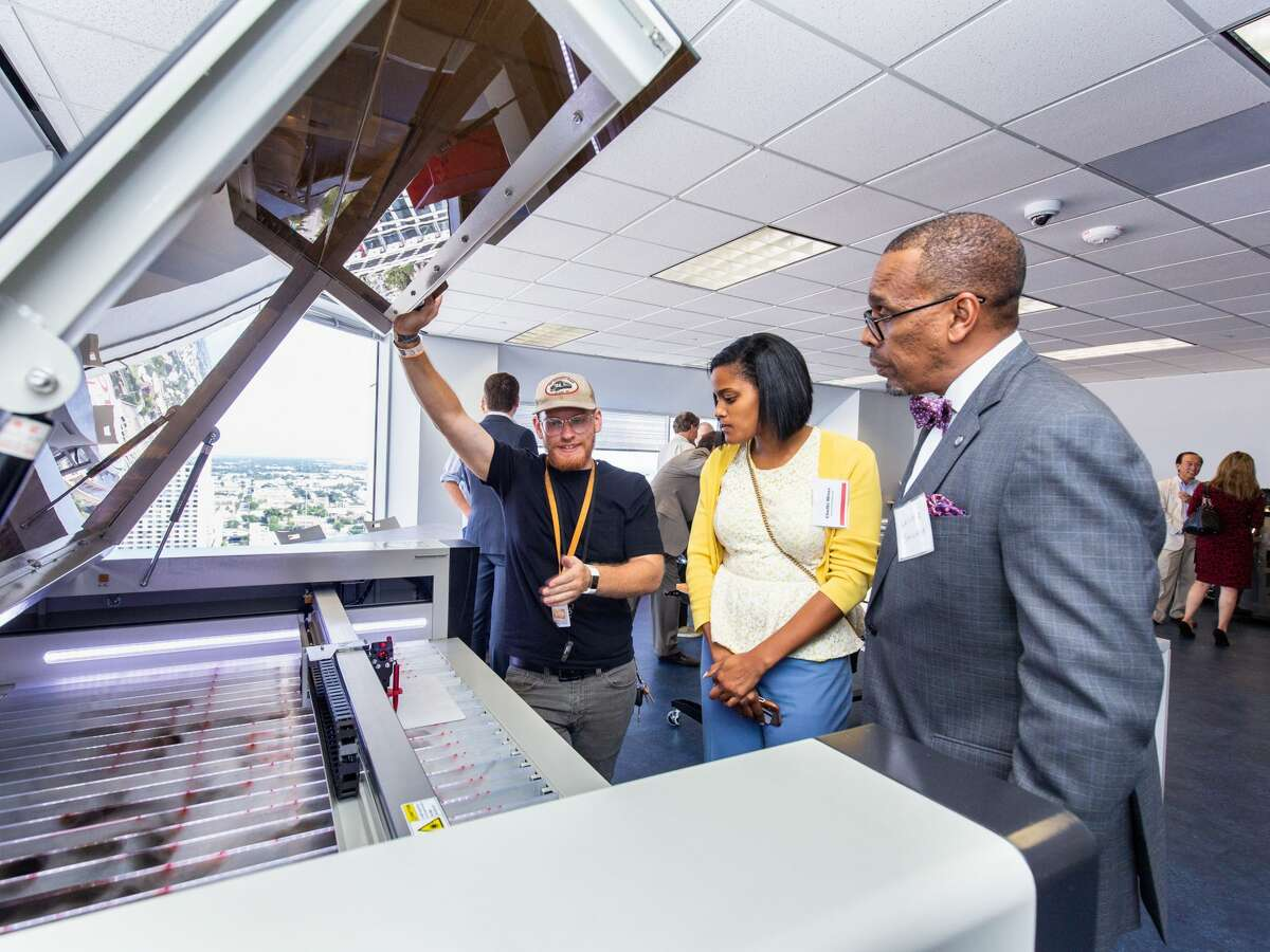 A TXRX Labs team member shows attendees the laser cutting machine in the makerspace. Station Houston has opened a prototyping lab and office space for the Ion Smart Cities Accelerator.