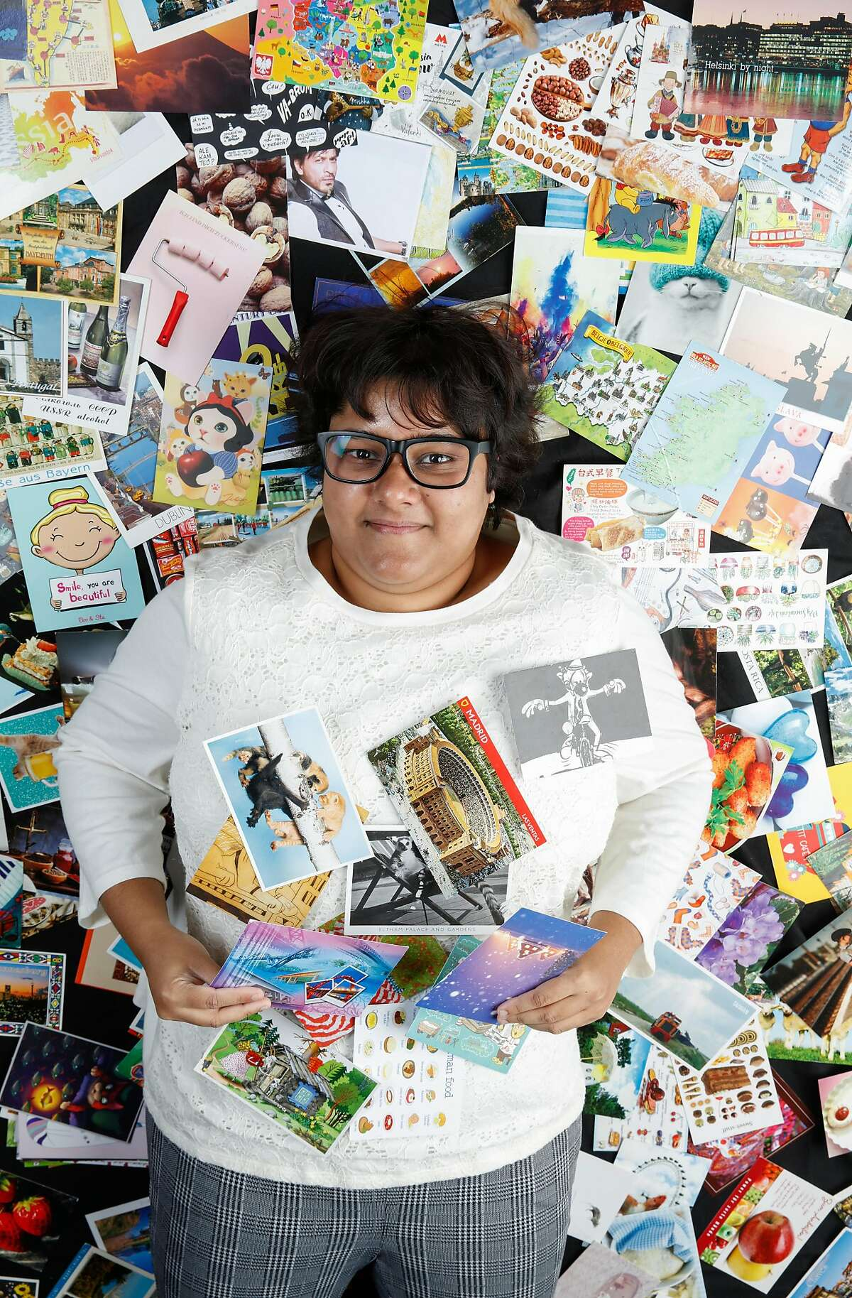 Rumana Sultana, who has been collecting postcards for years, cozies up to part of her collection of over 3,000 postcards.