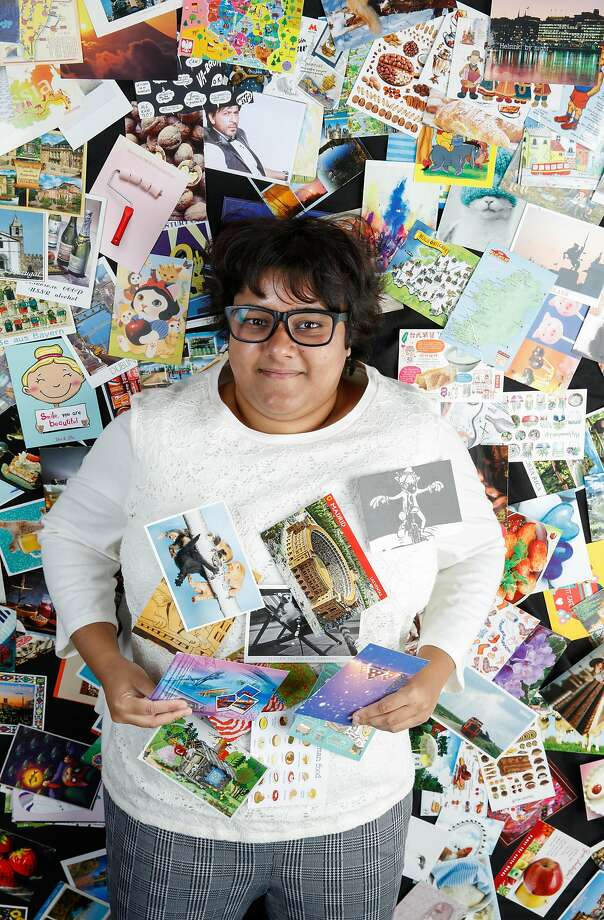 Rumana Sultana, who has been collecting postcards for years, cozies up to part of her collection of over 3,000 postcards. Photo: Russell Yip / The Chronicle