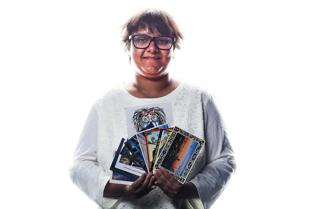 Rumana Sultana, who has been collecting postcards for years, holds a few.