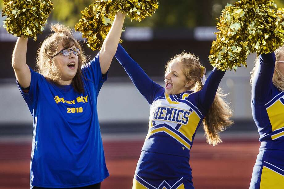 Midland High senior Amber Andrick, left, cheers alongside sophomore and varsity cheerleader Caelie Cervantes, center, during Victory Day, an event which gave students with special needs an opportunity to score a touchdown with the Chemics' football team or cheer with the cheer team, Monday, Sept. 23, 2019 at Midland Community Stadium. (Katy Kildee/kkildee@mdn.net) Photo: (Katy Kildee/kkildee@mdn.net)