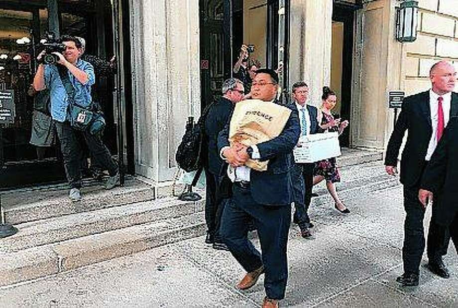 "A man carries a box marked ""evidence"" as he leaves the Capitol in Springfield on Tuesday. An FBI spokesman says agents are at the Capitol related to law enforcement work. The spokesman, John Althen, wouldn't provide details. Photo: John O'Connor 