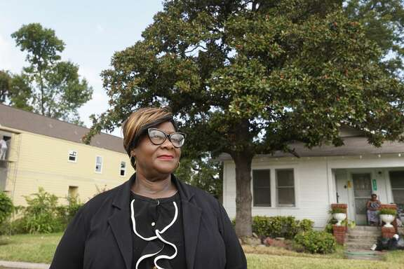 Tanya Debose, executive director of the Independence Heights Redevelopment Council, stands on East 30th Street in Independence Heights. In the background, new construction of a large two story home overshadows the historic home of Debra Brown.