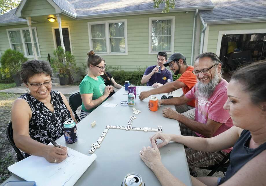 Ruth Sosa Bailey, left, her daughter, Elizabeth Sosa Bailey, Rachel Toombs, Nick Ocampo, Carlos Reyes, Steven Butera, and his wife, Shelby Butera, right, play dominoes in the Buteras' front yard in Independence Heights. Photo: Melissa Phillip/Staff Photographer
