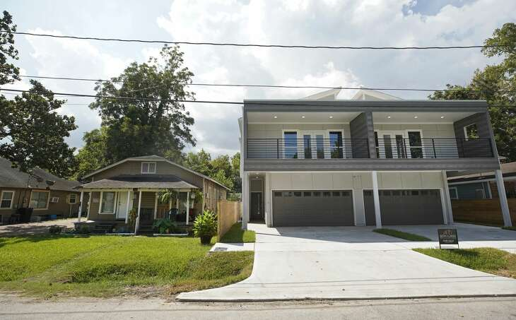 An older home is overshadowed by new home construction in Independence Heights. Despite efforts to preserve the community of Independence Heights, it is in danger of being lost to gentrification and development.