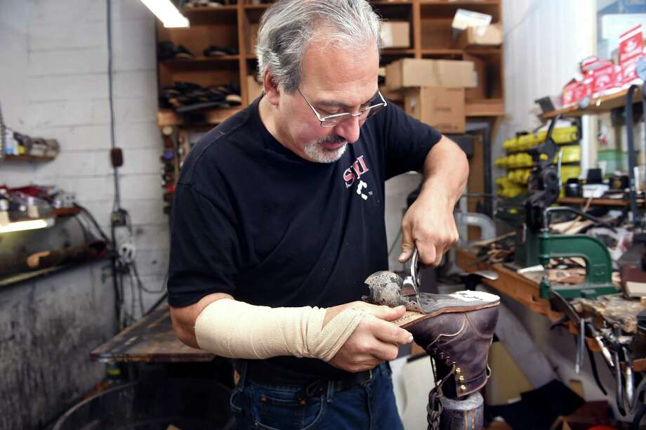 Michael Montalto removes a sole on a pair of Dayton boots at his store, M.T. Cobbler, in North Branford on Sept. 4. Photo: Arnold Gold / Hearst Connecticut Media / New Haven Register