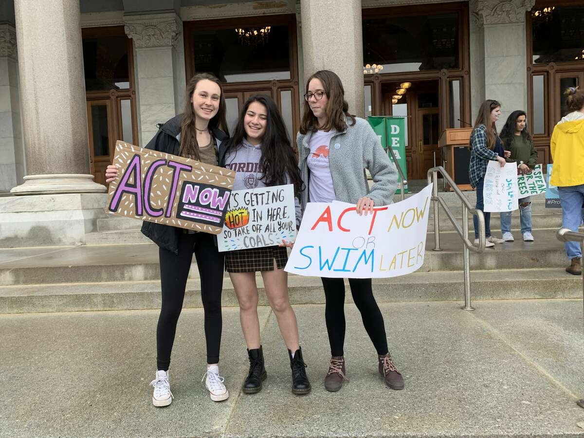 Ridgefield High School students Michaela Fitzgerald, Hannah Boylan, and Victoria Gibian hold up protest signs with environmentalist and author Leticia Colon de Mejias at the Youth Climate Strike in Hartford March 15.