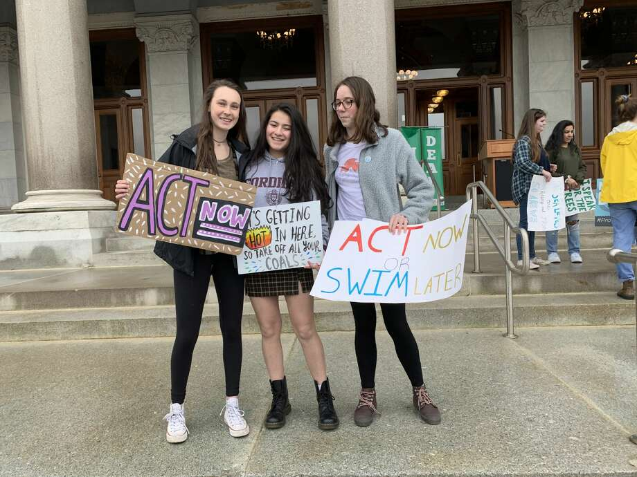 Ridgefield High School students Michaela Fitzgerald, Hannah Boylan, and Victoria Gibian hold up protest signs with environmentalist and author Leticia Colon de Mejias at the Youth Climate Strike in Hartford March 15. Photo: Contributed Photo