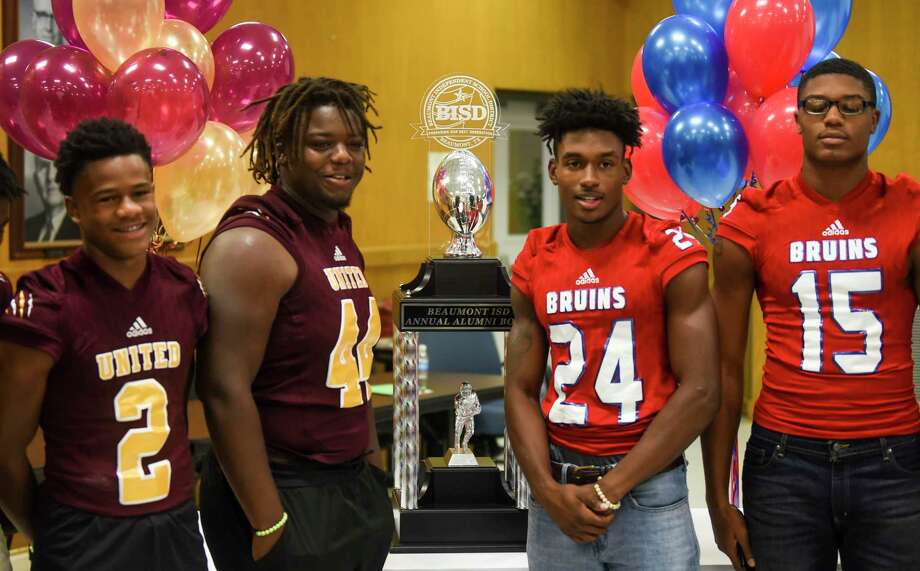 Players from both school pose in front of the trophy during the West Brook vs. United football press conference before the Alumni Bowl game in BISD's board room Wednesday. Photo taken on Wednesday, 09/18/19. Ryan Welch/The Enterprise Photo: Ryan Welch, Beaumont Enterprise / The Enterprise / © 2019 Beaumont Enterprise