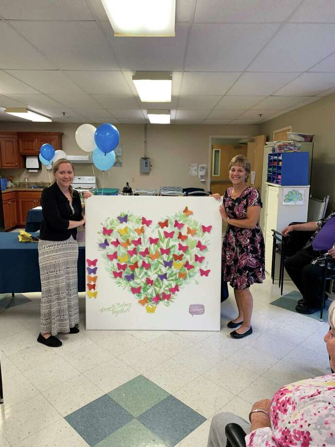 Atria Litchfield Hills residents are expressing gratitude in 100 different ways for the remaining 100 days of 2019. It's part of Atria's 100 Days of Gratitude challenge and the fourth annual Go Grateful campaign. Above, Kelly Bossidy, left, presents her residents' art to Pam Brunoli, Recreation Director at Litchfield Woods Health Care during a reception earlier this month. Photo: Atria Litchfield Hills / Contributed Photo /