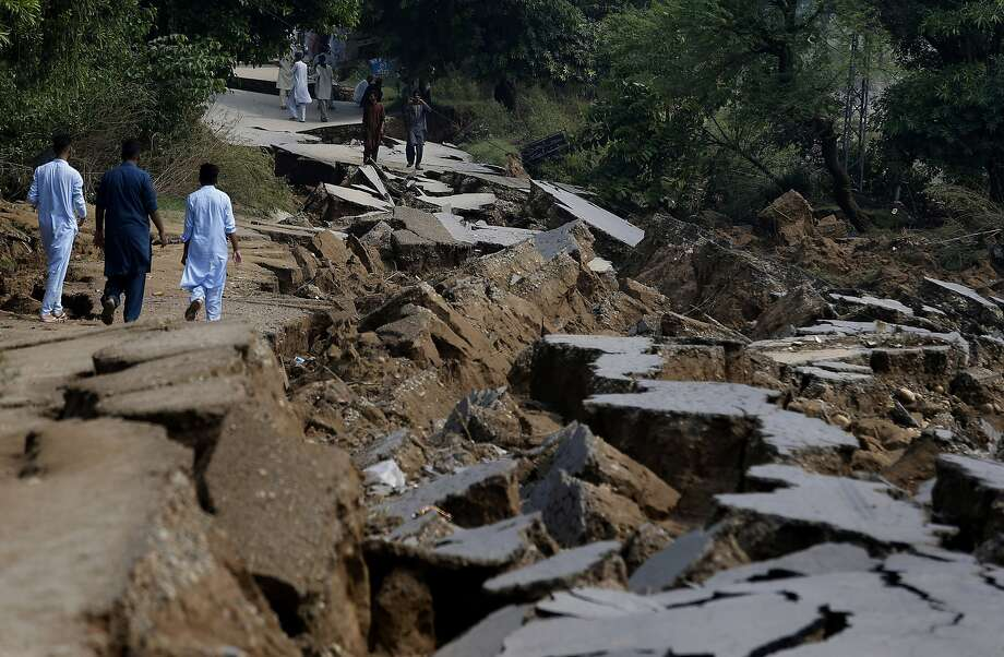 Residents walk alongside a damaged portion of a road caused by a powerful 5.8 magnitude earthquake in near Mirpur, in Pakistan-held Kashmir. Some 37 people have been killed. Photo: Anjum Naveed / Associated Press