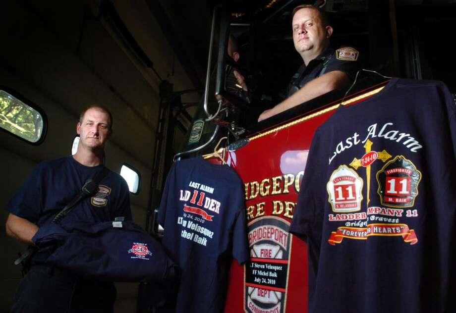 Bridgeport Fire Lt. Ron Rolfe, left, and Lt. Matt Deysenroth, right, display T-shirts that the Bridgeport Fire Department is selling to benefit the Bridgeport Fallen Firefighters Fund to help support the families of Firefighter Lt. Steven Velasquez and Firefighter Michel Baik.  Rolfe and Deysenroth designed the backs of the two shirts available for sale.  T-shirts will be on sale at the Orange Firemans Carnival this Sunday.  For information on purchasing a shirt, visit local834.org. Photo: Autumn Driscoll / Connecticut Post