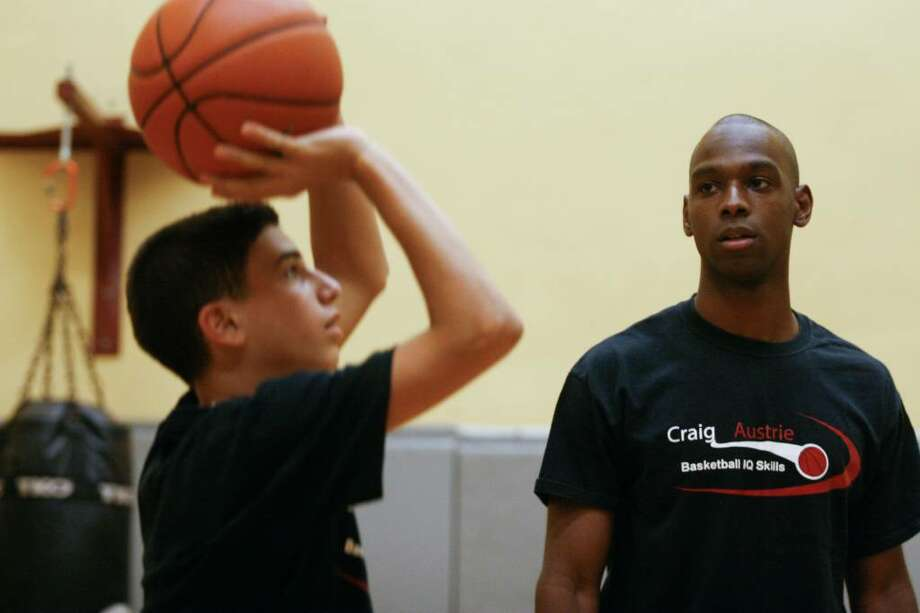 Craig Austrie, former UConn basketball player, watches as Lucas Salem, age 13, practices during a coaching session at the Stamford Sportsplex on Wednesday, August 4, 2010. Photo: Laura Buckman / Connecticut Post
