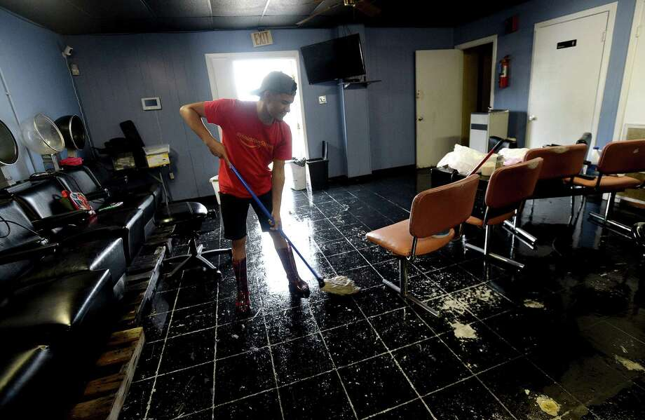 Coreyy Vee sweeps the flooded floor of Cuts and Curls on S. 4th Street in Beaumont as the process of recovery from Imelda's torrential rains and flooding begins throughout the region Friday. Photo taken Friday, September 20, 2019 Kim Brent/The Enterprise Photo: Kim Brent / The Enterprise / BEN