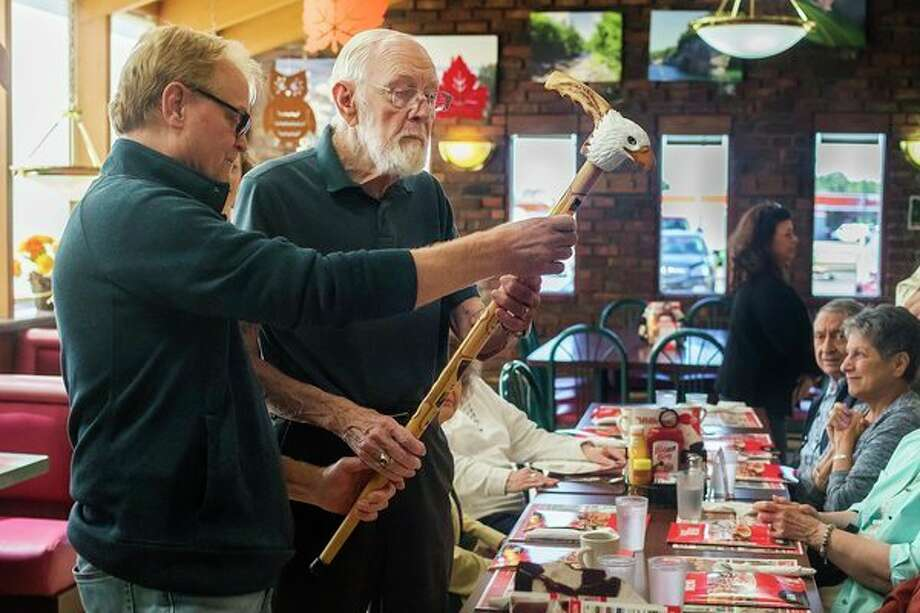 World War II veteran Jack Harper, 91, right, takes a look at a custom hand-carved cane after he was surprised with the gift by his son, Jack Harper II, left, during a weekly gathering of friends this week at Big Boy in Midland. For more photos, visit www.ourmidland.com. (Katy Kildee/kkildee@mdn.net)