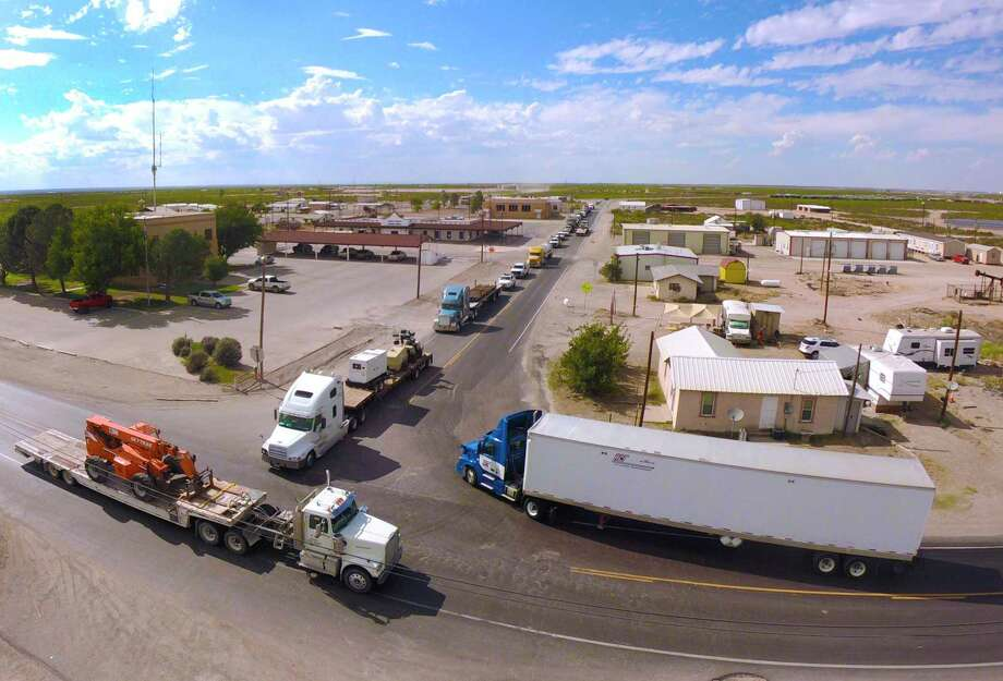 Heavy truck traffic travels the streets in Mentone. The population swells to as many as 10,000 daily when workers arrive to labor in energy industry facilities. Photo: Billy Calzada /Staff Photographer / San Antonio Express-News