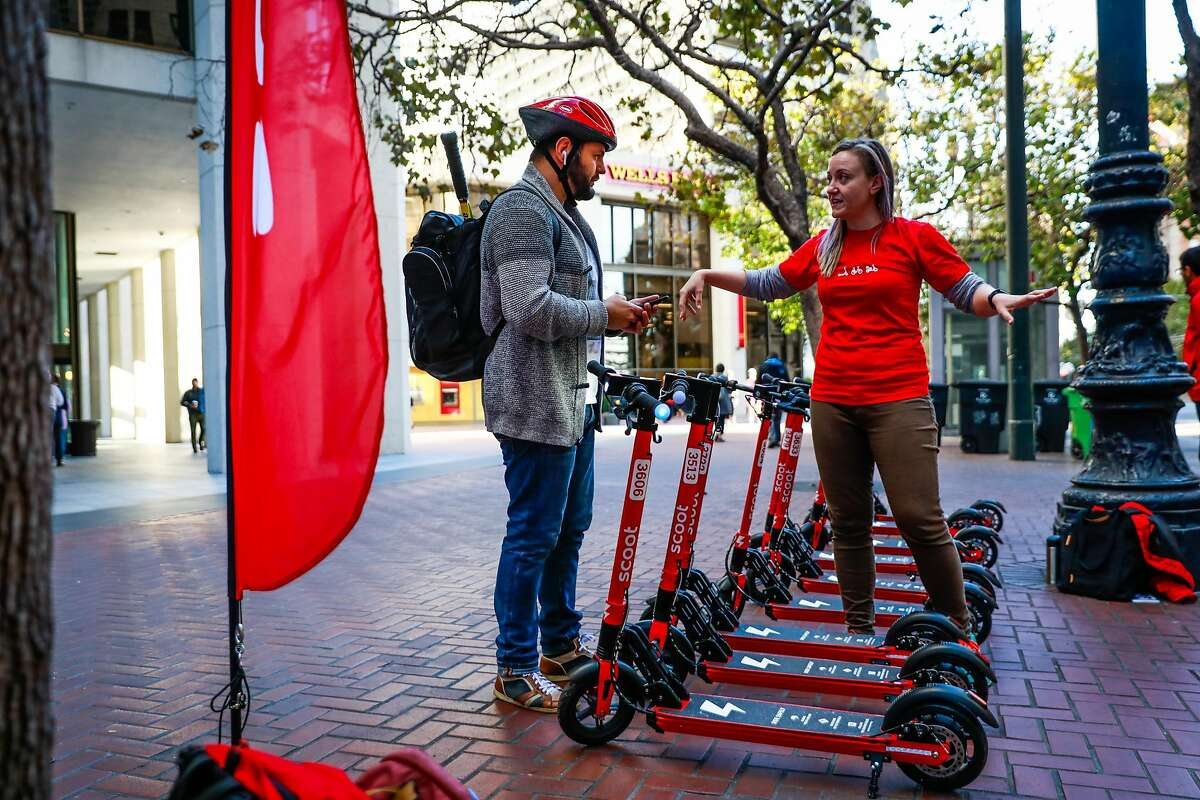 Andriy Fedorchuk chats with Scoot employee Jessie Greger (right) before taking a spin on a Scoot scooter in San Francisco, California, on Monday, Oct. 15, 2018.
