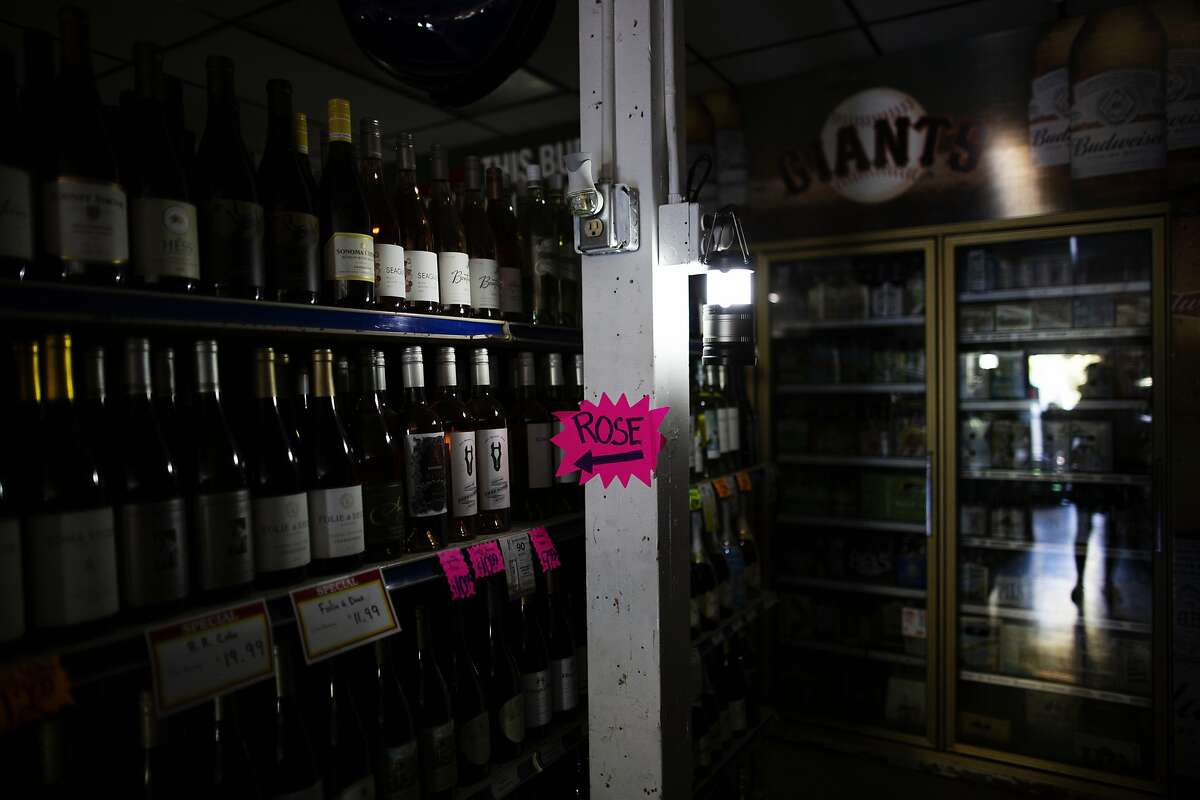 A lantern lights an isle of wine at the Calistoga Liquor, that had its electricity cut by PG&E in attempts to prevent fires during extreme fire conditions,Calistoga, September 25th, 2019. PG&E shut off electricity to parts of Calistoga in attempts to prevent fire started by their lines during extreme fire conditions. The first report of the Tubbs Fire came from Hwy 128 and Tubbs lane -where Calistoga Liquor store is located.