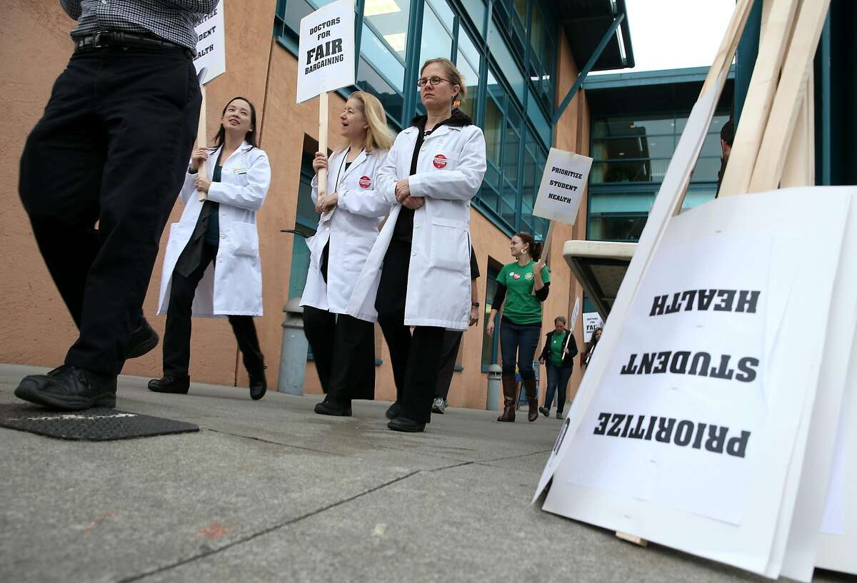 Medical doctors Leslie Gee (left), Annie Hope (center), and Odile Arizmendi on a picket line in front of the University Health Services clinic at UC Berkeley during a one-day strike on all ten University of California campuses in 2015. Contra Costa County doctors may strike for the first time in their union's history as early as next month.