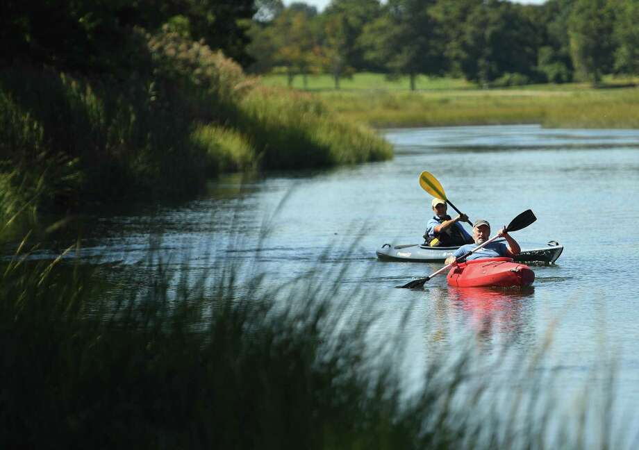 Friends Gary Nichols, left, and David Thornton, both of Fairfield, kayak on scenic Mill Creek in Westport on Tuesday. Mill Creek forms the border of Sherwood Island State Park. Photo: Brian Pounds / Hearst Connecticut Media / Connecticut Post