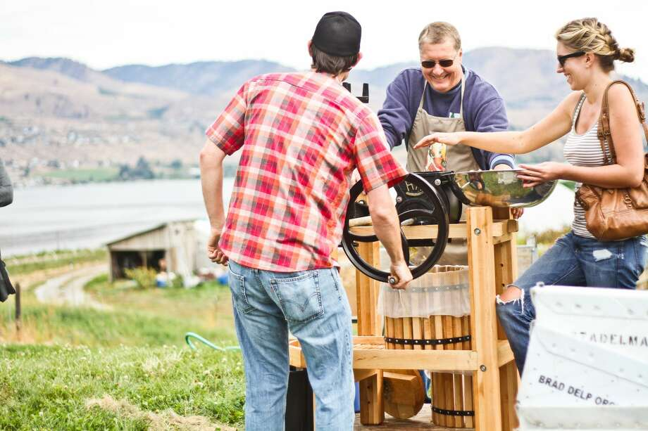 Visitors hand-crank their cider at the Sunshine Farm Market. Photo: Kirsten J. Cox, Courtesy Of Lake Chelan Chamber Of Commerce