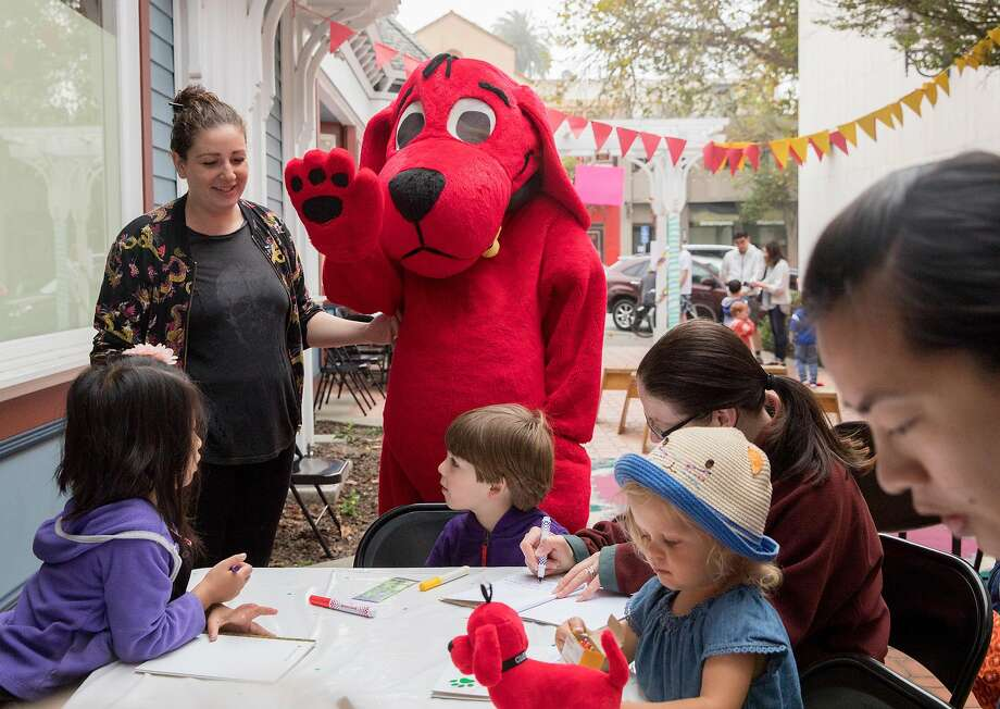 Clifford the Big Red Dog greets kids attending the West Portal Book Festival. Events are crucial for drawing foot traffic, merchants say. Photo: Jessica Christian / The Chronicle