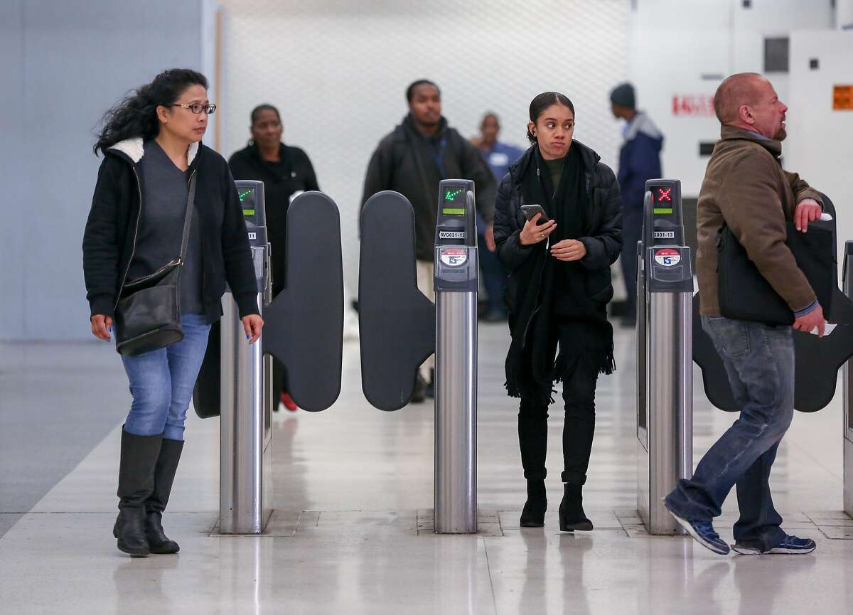 Passengers enter and exit through the muni gates at Powell station on Monday, November 29, 2016.