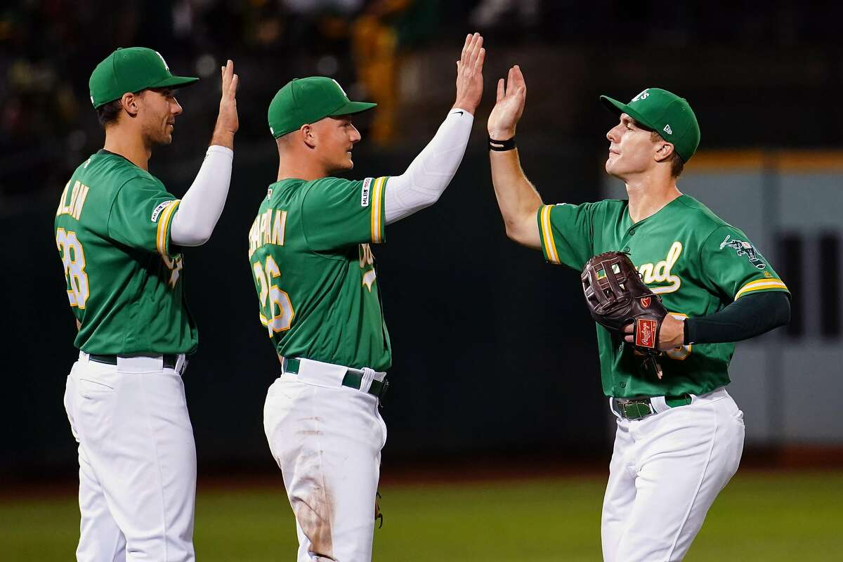 OAKLAND, CALIFORNIA - SEPTEMBER 20: Matt Olson #28 and Matt Chapman #26 celebrate with Mark Canha #20 of the Oakland Athletics after beating the Texas Rangers at Ring Central Coliseum on September 20, 2019 in Oakland, California. (Photo by Daniel Shirey/Getty Images)