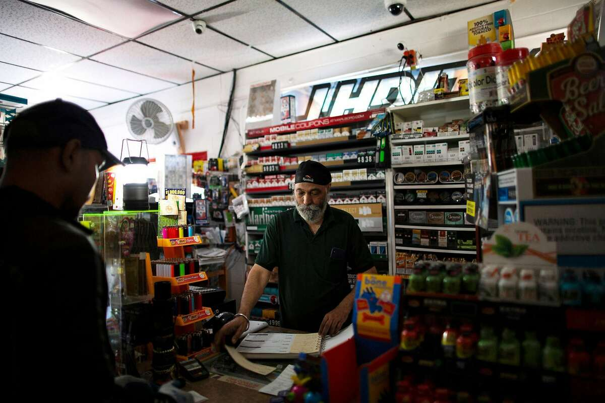 """Gormeet Singh (known as """"Monty"""") the manager at Calistoga Liquor finishes an order with 7-Up deliverer David Thach at the Calistoga Liquor store during a power outage that PG&E is doing attempts to prevent fire during extreme fire conditions, Calistoga, September 25th, 2019. PG&E shut off electricity to parts of Calistoga in attempts to prevent fire started by their lines during extreme fire conditions. The first report of the Tubbs Fire came from Hwy 128 and Tubbs lane -where Calistoga Liquor store is located."""