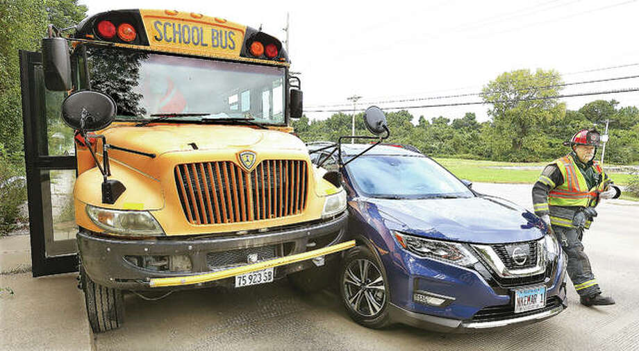 A Nissan Rogue, right, crashed into the front end of a school bus full of students in Alton around 2 p.m. Wednesday. Alton Police said the Nissan Rogue was pulling out into the southbound lane of Humbert Road when it crossed the path of a northbound motorcycle, causing the operator to fall onto the road. The Nissan continued into the southbound lanes, striking the bus near the driver's seat.