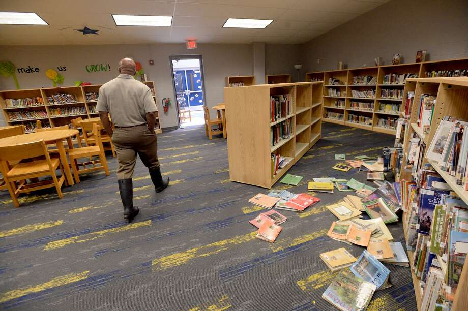 """Hamshire-Fannett Superintendent Dwaine Augustine shows the damage to the Intermediate school building, which along with the middle school flooded after Imelda's heavy rainfall. He says the school got about 15"""" of water inside, some of which remained pooling on the floor in spots Wednesday. Photo taken Wednesday, September 25, 2019 Kim Brent/The Enterprise Photo: Kim Brent/The Enterprise"""