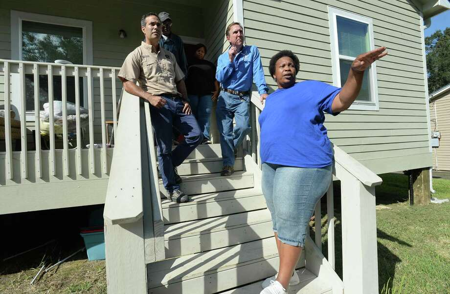 Texas Land Commissioner George P. Bush and Jefferson County Judge Jeff Brannick talk with Carmaro Hervey, as her husband George and daughter Kandice Zem listen at the porch of the Hervey's HAP home on Hybrook Lane in Beaumont Wednesday. The family's elevated home, built after losing theirs to flooding during Harvey, did not flood and became a refuge for neighbors whose homes came within inches of flooding during Imelda. Bush made the stop while in the area to survey damage in Chambers County from the recent storm.  Photo taken Wednesday, September 25, 2019 Kim Brent/The Enterprise Photo: Kim Brent / The Enterprise / BEN