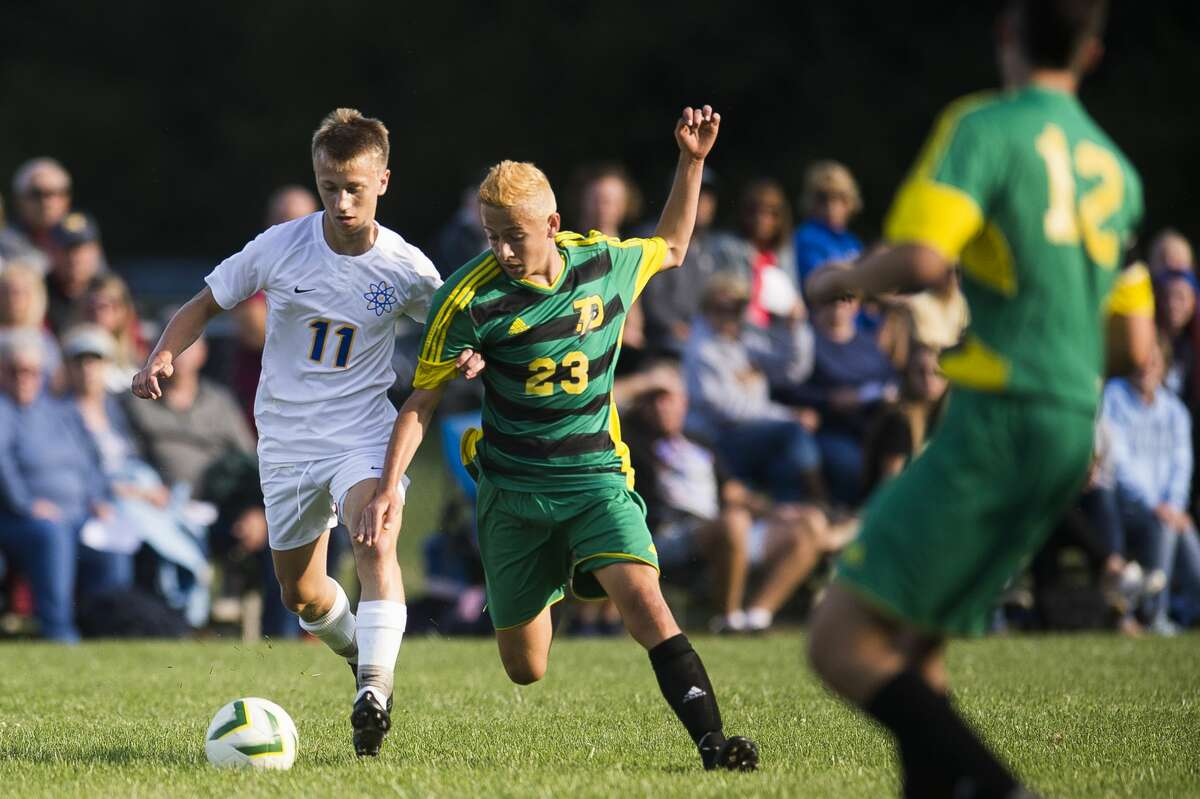 Midland's Brett Waskevich and Dow's Ethan Swartzentruber fight for possession during their game Wednesday, Sept. 25, 2019 at H. H. Dow High School. (Katy Kildee/kkildee@mdn.net)