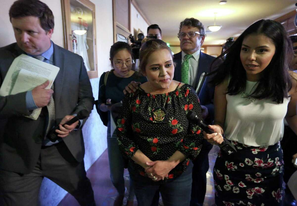 Bexar County Precinct 2 Constable Michelle Barrientes Vela, center, leaves the Bexar County Commissioners Court Wednesday, Sept. 25, 2019 flanked by the media and followed by her attorney, Leslie Sachanowicz, after listening to a news conference from County Judge Nelson Wolff. Wolff announced that Vela's public statements indicating she would be running for sheriff triggered the state constitution's