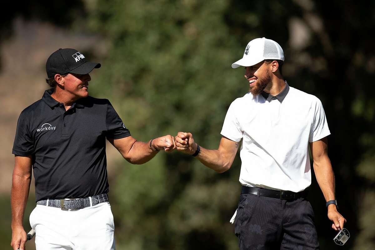 Phil Mickelson, left, and Golden State Warriors star Stephen Curry share a fist bump during the Safeway Open pro-am golf event on Wednesday, Sept. 25, 2019 in Napa, Calif.