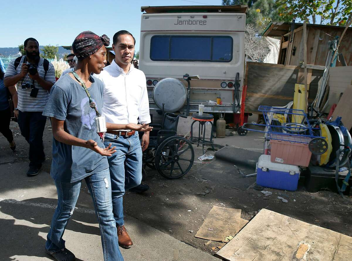 Markaya Spikes, a resident of a homeless encampment near the Home Depot off High Street for five years, leads former Secretary of Housing and Urban Development and Democratic presidential candidate Julian Castro on a tour of the camp in Oakland, Calif. on Wednesday, Sept. 25, 2019.