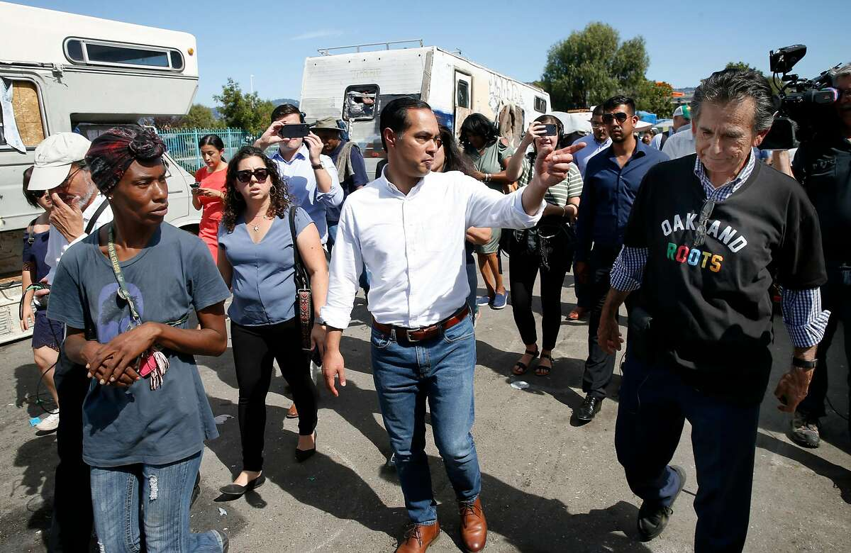 Former Secretary of Housing and Urban Development and Democratic presidential candidate Julian Castro tours a homeless encampment with camp resident Markaya Spikes (left) and city council member Noel Gallo near the Home Depot at High Street in Oakland, Calif. on Wednesday, Sept. 25, 2019.