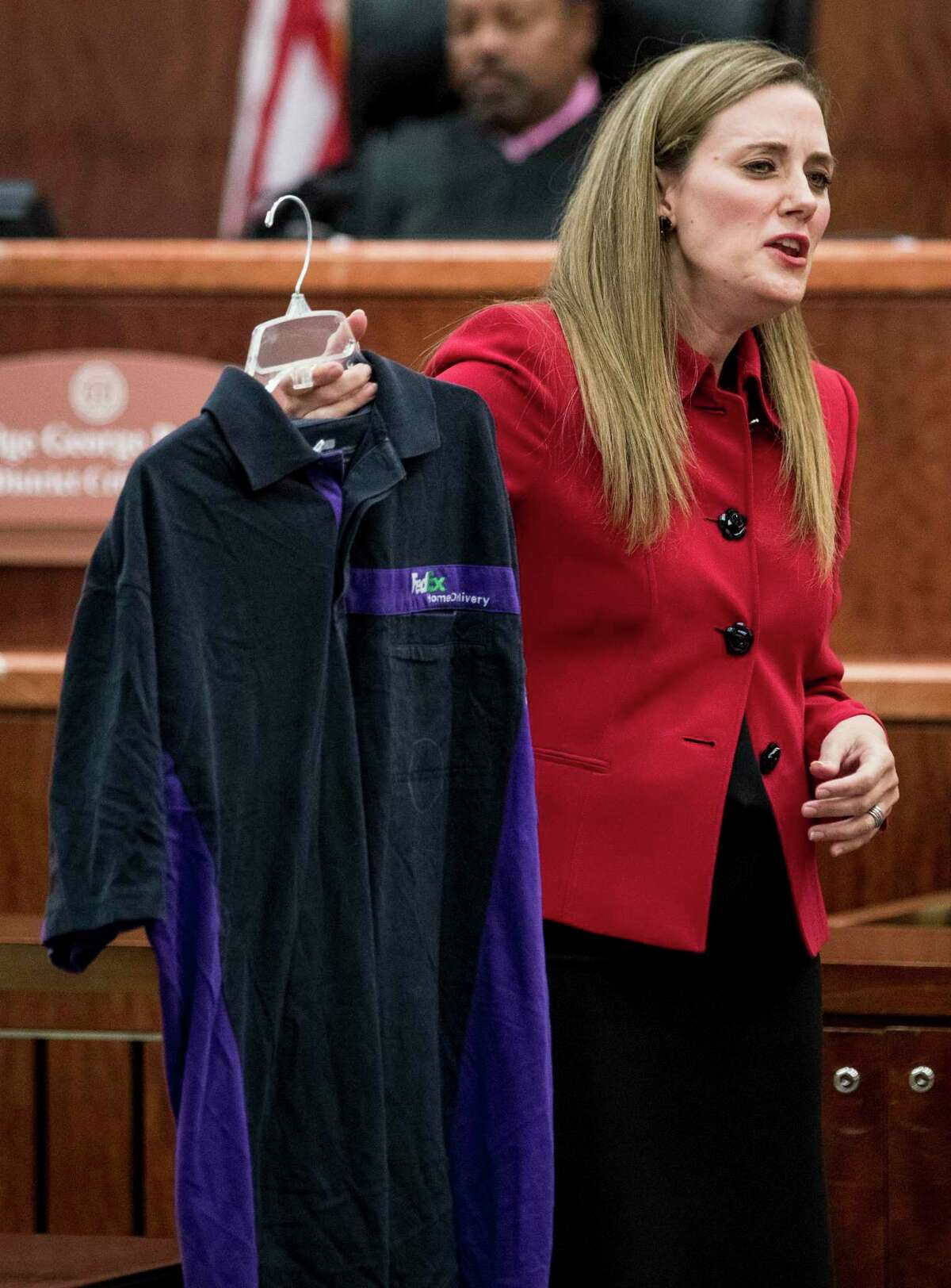 Prosecutor Samantha Knecht holds up a FedEx shirt, which was entered as evidence earlier in the trial, during the closing arguments in Ronald Haskell's capital murder trial on Wednesday, Sept. 25, 2019, in Houston. Haskell is charged with capital murder in connection with the 2014 massacre of a Spring family.