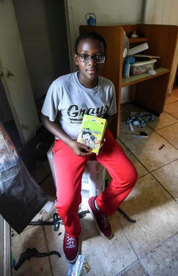Drarey Jackson, 12, holds his favorite book that was damaged by floodwater as he poses for a photo in his room in his house on Clearview Street in Beaumont Wednesday. Photo taken on Wednesday, 09/25/19. Ryan Welch/The Enterprise Photo: Ryan Welch, Beaumont Enterprise / The Enterprise / © 2019 Beaumont Enterprise