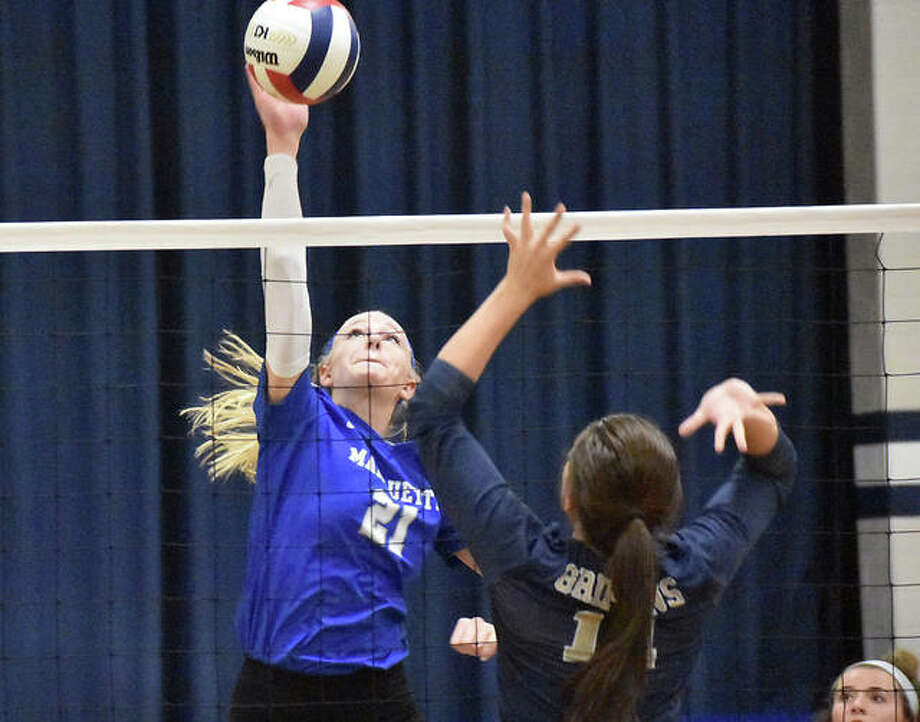 Marquette's Emma Menke (left) attacks during the Explorers' two-set win over Father McGivney on Wednesday in Alton. Photo: Matt Kamp / Hearst Illinois