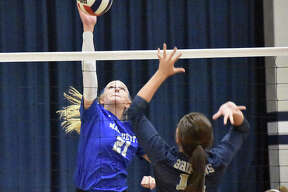 Marquette's Emma Menke (left) attacks during the Explorers' two-set win over Father McGivney on Wednesday in Alton.