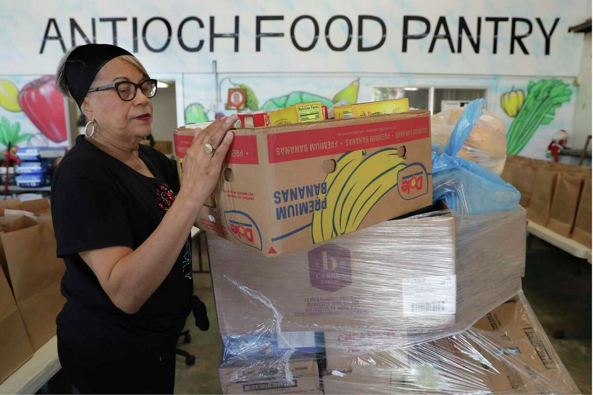 Joyce Robinson, a volunteer at the Food Bank at Antioch Missionary Baptist Church, unloads a box of food delivered by the San Antonio Food Bank on Sept. 25, 2019.