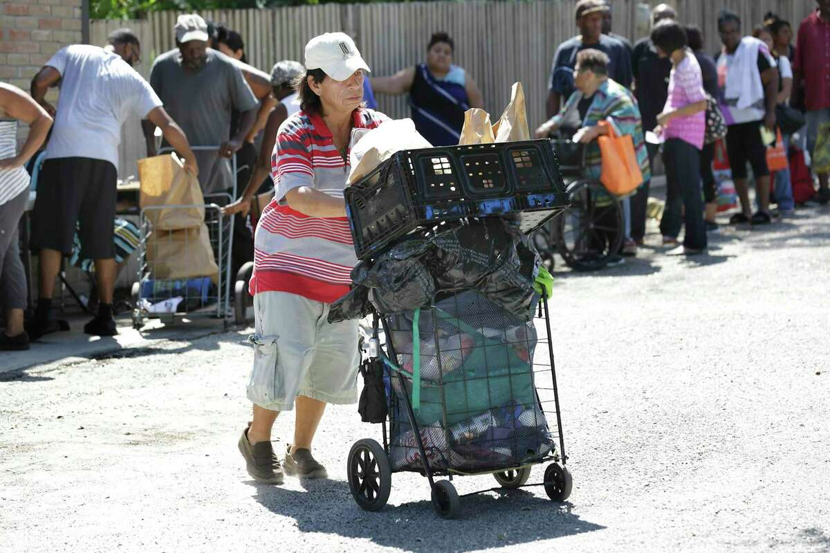 A food recipient wheels a cart as the line looms behind at the Food Bank at Antioch Missionary Baptist Church this September. It's simple to feed people who are hungry. Addressing poverty is a far more complex endeavor.