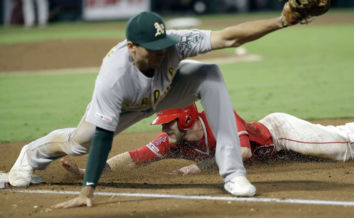 Los Angeles Angels' Taylor Ward, back, iis out at first base after a fly out by Kaleb Cowart and a throw to Oakland Athletics first baseman Matt Olson from right fielder Ramon Laureano during the fourth inning of a baseball game Wednesday, Sept. 25, 2019, in Anaheim, Calif. (AP Photo/Marcio Jose Sanchez)