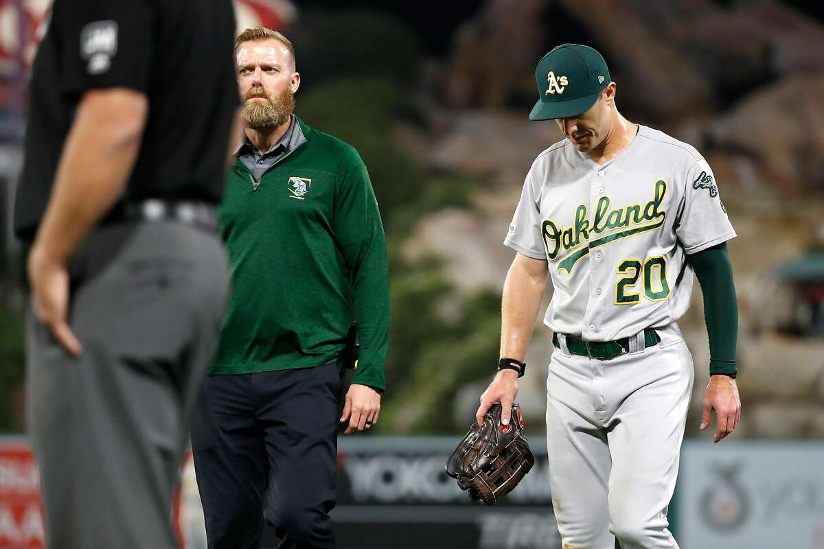 ANAHEIM, CALIFORNIA - SEPTEMBER 25: Mark Canha #20 of the Oakland Athletics walks off the field after he was injured chasing down a fly ball during the seventh inning of a game against the Los Angeles Angels of Anaheim at Angel Stadium of Anaheim on September 25, 2019 in Anaheim, California. (Photo by Sean M. Haffey/Getty Images)