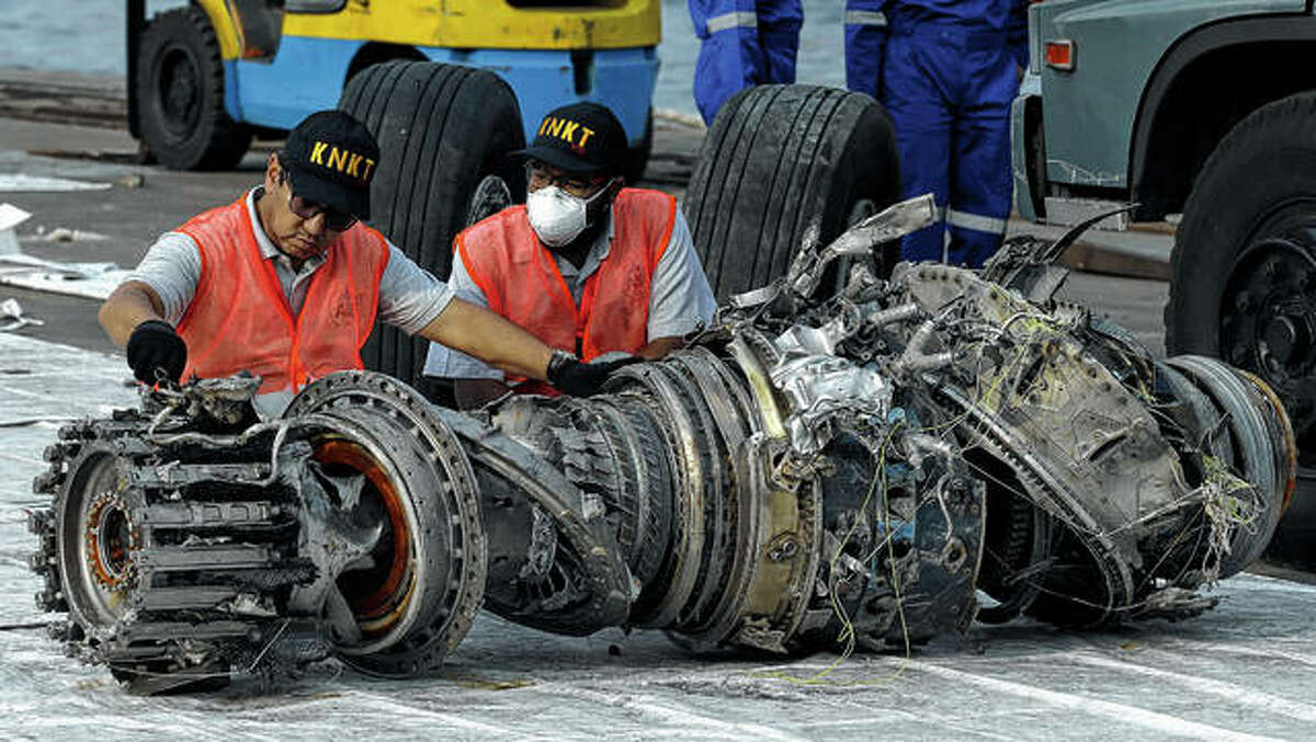 Officials inspect in November an engine recovered the crashed Lion Air jet in Jakarta, Indonesia. A Chicago law firm says it has settled lawsuits against Boeing on behalf of the families of 11 passengers killed in the crash of the Lion Air jet off the coast of Indonesia.