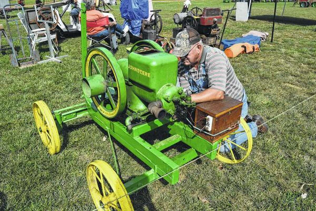 """Norm Werts of Virginia works Sept. 26, 2018, on a fuel line on a John Deere 3-horsepower """"hit and miss"""" engine on the Prairie Land Heritage Museum grounds in South Jacksonville. The farm museum's 50th annual Fall Festival & Steam Show Days will be Friday, Saturday and Sunday."""
