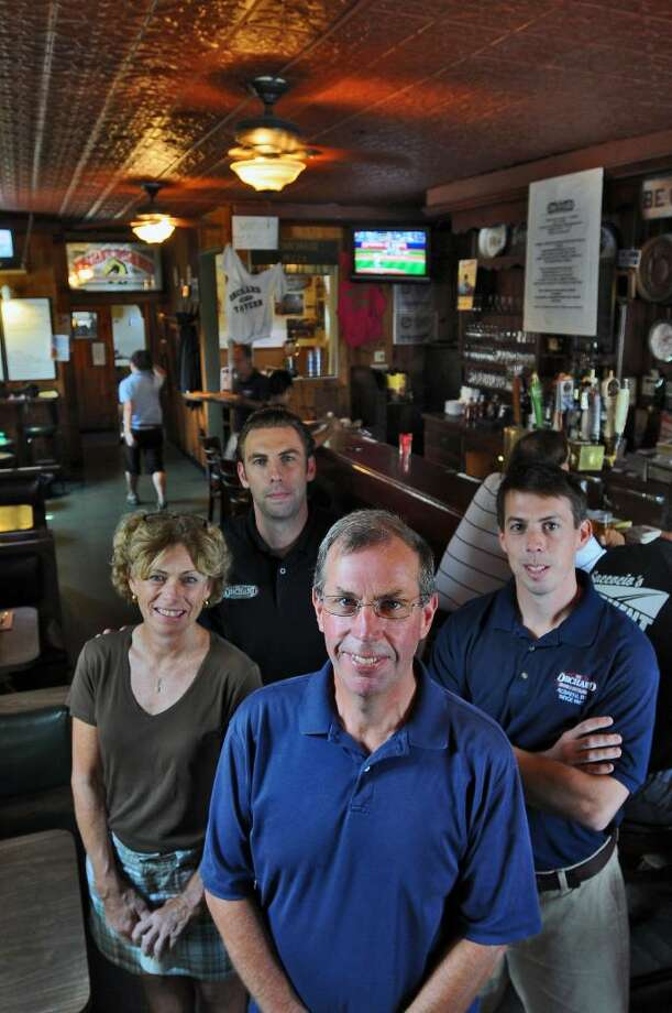 Mike Noonan, center foreground, changed his mind about selling The Orchard Tavern & Restaurant on North Manning Boulevard in Albany, NY, now that his sons Patrick, second from left, and Brendan, far right, are working with Mike and his wife (and the boy's mother) Karen, left,  shown in the bar  on Wednesday August 4, 2010.   (Philip Kamrass / Times Union) Photo: PHILIP KAMRASS / 00009730A