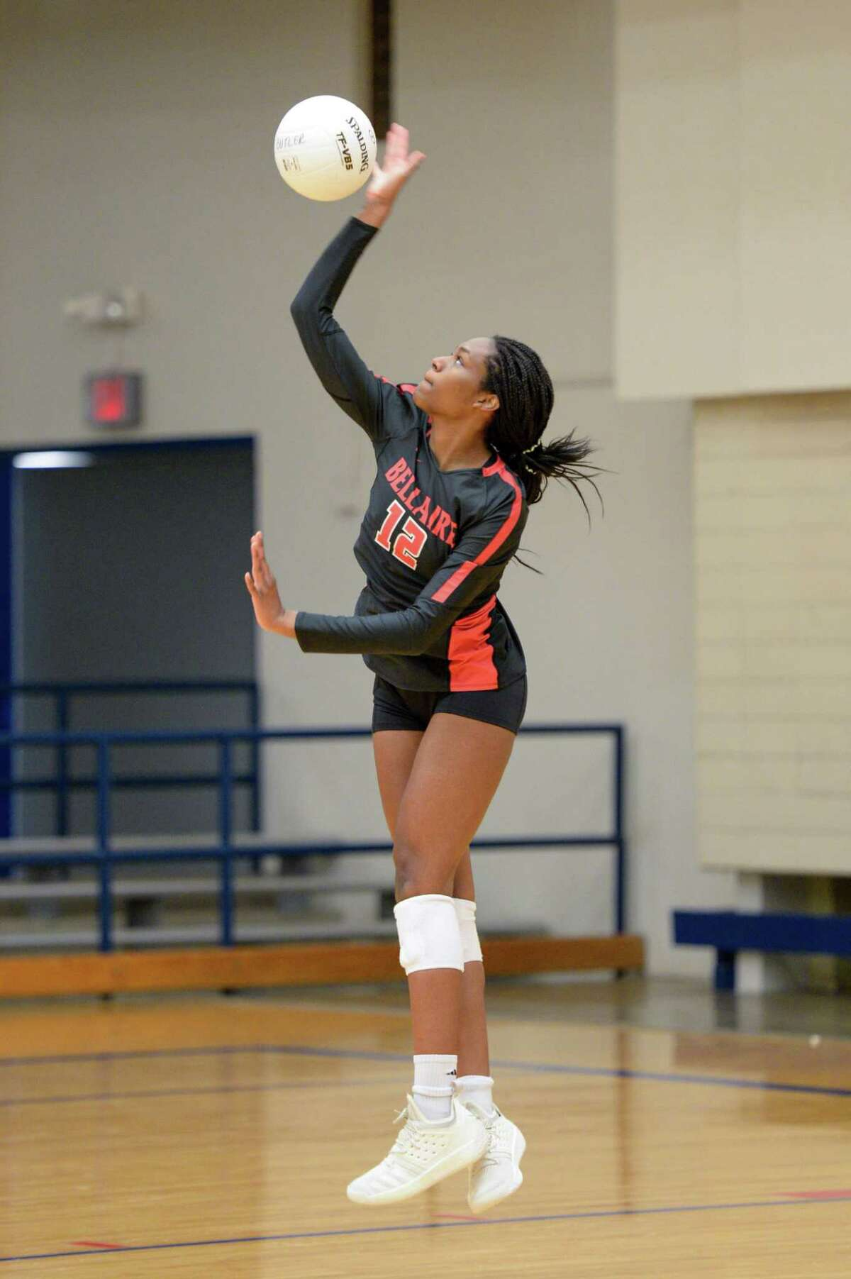 Starr Martin (12) of Bellaire serves a ball during the second set of a high school volleyball match between the Bellaire Cardinals and the Chavez Lobos on Tuesday, September 24, 2019 at Butler Fieldhouse, Houston, TX.