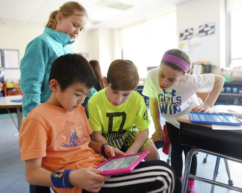 Fourth-graders Ibuki Matsushita, left, Will Duncan, Logan Gilbrid and Tori Ware, right, work on an iPad during math class at North Mianus School in Greenwich, Conn. Wednesday, April 1, 2015. Students and teachers use the Singapore math program, which uses concrete, pictoral and abstract steps and places emphasis on critical thinking and collaboration. Photo: Tyler Sizemore / Tyler Sizemore / Greenwich Time